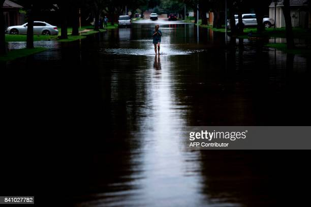 TOPSHOT A woman walks down a flooded road during the aftermath of Hurricane Harvey on August 30 2017 in Houston Texas Monster storm Harvey made...
