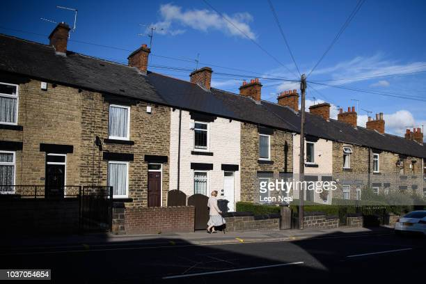 Woman walks down a row of traditional terraced houses on September 18, 2018 in Barnsley, England. The area around Barnsley is made up of many smaller...