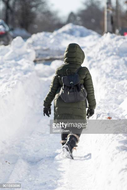 A woman walks down a shoveled path alongside the road the day after the region was hit with a 'bomb cyclone' on January 5 2018 in the Dorchester...