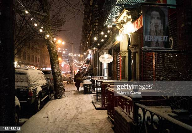 Woman walks down a sidewalk under hanging lights in the East Village as snow falls during a winter storm.