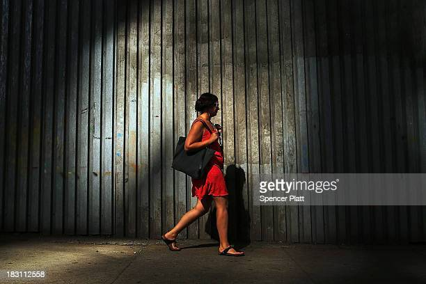 A woman walks down a street in Dumbo on October 4 2013 in the Brooklyn borough of New York City A group of five prominent properties in Dumbo owned...