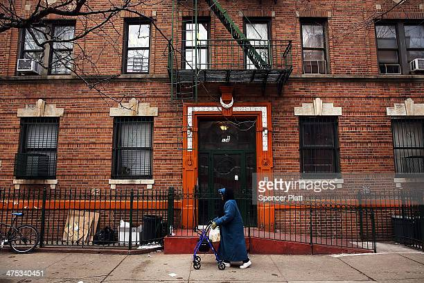 Woman walks down a street in the Fort Greene neighborhood where the director and artist Spike Lee once lived on February 27, 2014 in the Brooklyn...