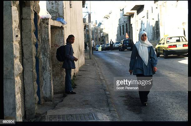 A woman walks down a street May 17 1998 in Amman Jordan Still a teenager when crowned in 1952 King Hussein has led the young Arab nation through...