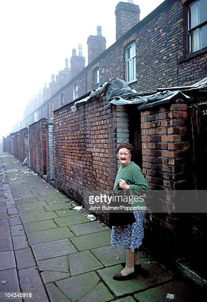 A woman walks down an alleyway between terraced brick streets in Manchester England in 1976