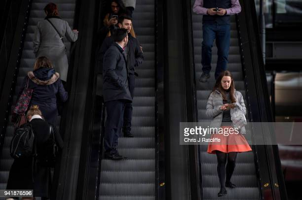 A woman walks down an escalator outside the Leadenhall Building as the deadline nears for companies to report their gender pay gap on April 4 2018 in...