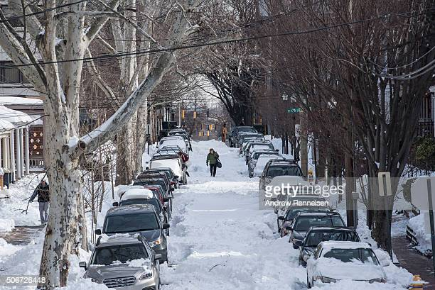 Woman walks down an un-plowed road following a blizzard on January 25, 2016 in Wilmington, Delaware. Many streets in the city remained covered with...