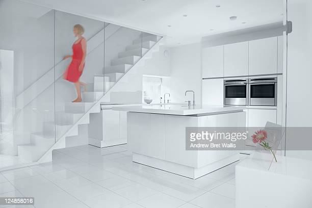 woman walks down stairs of a contemporary home - caucasian ethnicity stock pictures, royalty-free photos & images