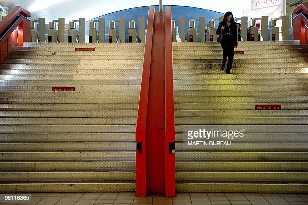 A woman walks down stairs on March 23 2010 at the Auber suburban train station in Paris as French public sector workers including transport workers...