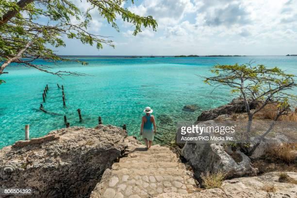 woman walks down steps towards secluded cove - aruba stockfoto's en -beelden