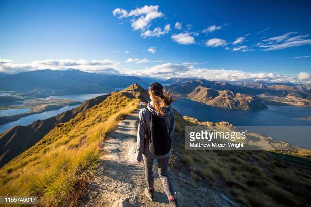 a woman walks down the trail on the roy's peak hike. - new zealand bildbanksfoton och bilder