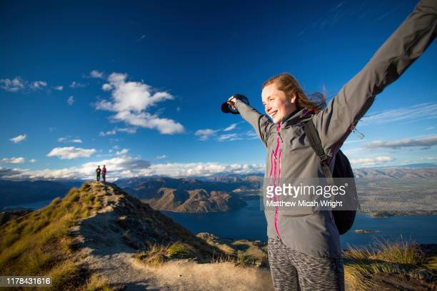 a woman walks down the trail on the roy's peak hike. - summit stock pictures, royalty-free photos & images