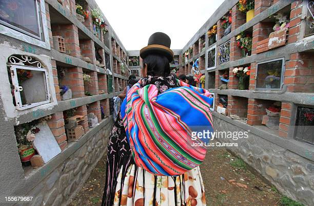 A woman walks during the traditional celebration Feast of all Saints where families reunite in the cementery with the belief that the soul will visit...