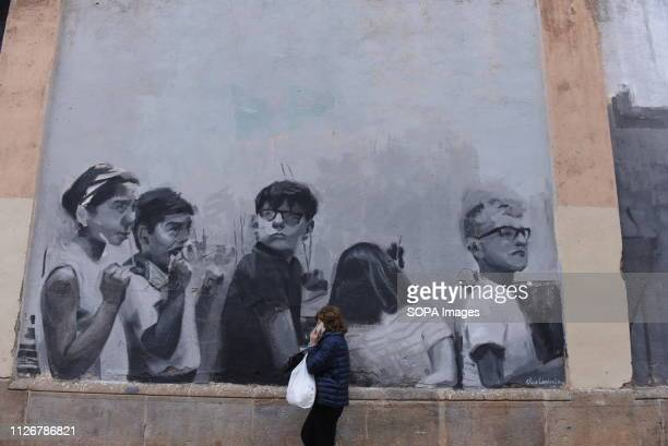 A woman walks front of a murals painting at 'La Modelo' prison in Barcelona