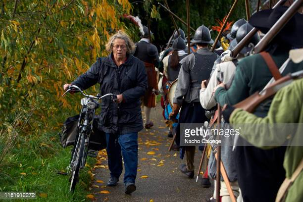 A woman walks her bicycle past the battle participants on October 18 2019 in Groenlo Netherlands For three days the streets of the village of Groenlo...