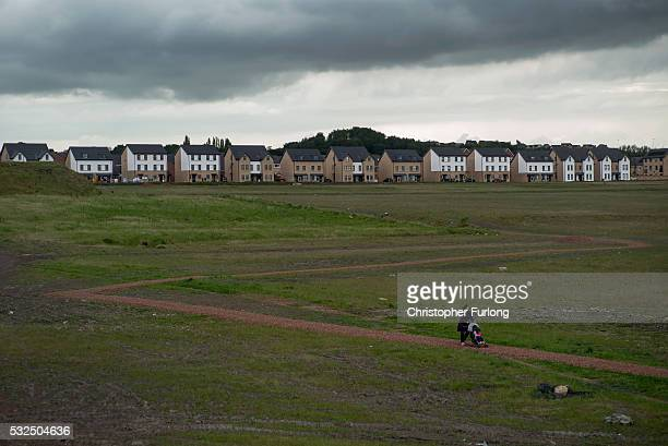 A woman walks her child on the reclaimed land of the former Orgreave Coking plant which has now been redeveloped for modern housing as the coking...