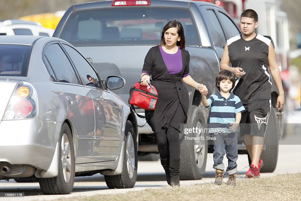 A woman walks her children to her car, because area intermediate and elementary schools were on lockdown after a shooting occurred at Lone Star College Campus on January 22, 2013 in The Woodlands, Texas. According to reports, three people were injured during a shooting on the courtyard between the Library and cafeteria.