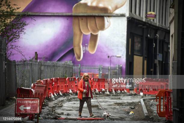 A woman walks her dog in Mitchell Lane as the country goes into lockdown on March 24 2020 in Glasgow Scotland First Minister of Scotland Nicola...