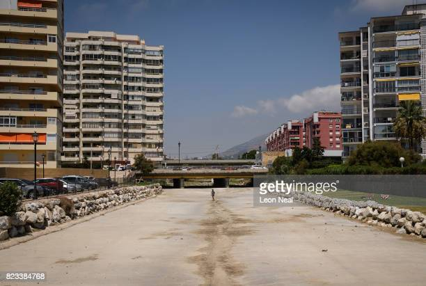 A woman walks her dog in the driedup river bed on July 25 2017 in Fuengirola Spain With Brexit discussions yet to provide answers to a number of...