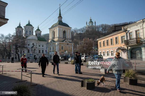 A woman walks her dog near a polling station in Kiev Ukraine on Sunday March 31 2019 Ukrainians will choose between a field of almost 40 candidates...