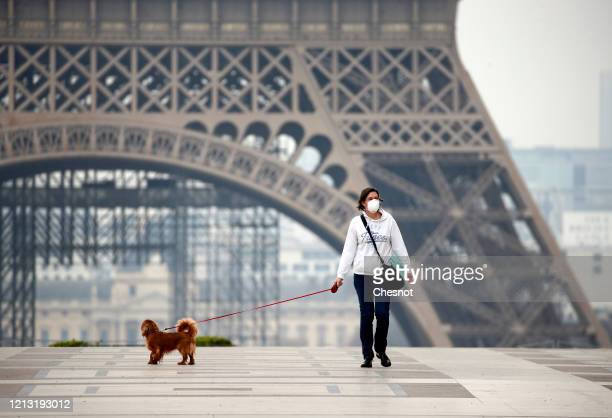 A woman walks her dog on the Esplanade du Trocadero square in front of the Eiffel Tower the second day after the announcement by French President...