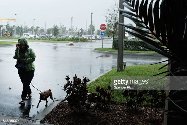 A woman walks her dog outside of a hotel as Hurricane Irma arrives into southwest Florida on September 10 2017 in Fort Myers Florida With businesses...