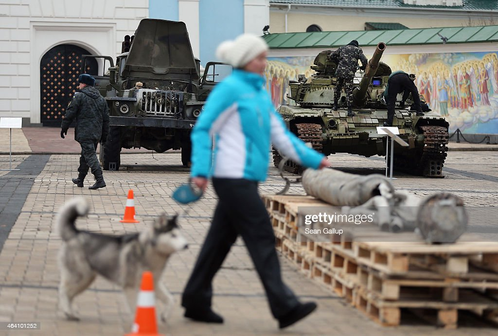 A woman walks her dog past a rocket launcher truck, a heavy tank and the remains of a missle that are part of an exhibition the Ukrainian government claims proves Russian direct involvement in the fighting between Ukrainian troops and pro-Russian separatists in eastern Ukraine on February 22, 2015 in Kiev, Ukraine. Russia has denied sending heavy weaponry to the separatists, admitting only that Russian volunteers are participating in the fighting.