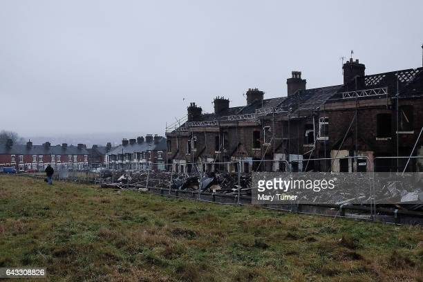 Woman walks her dog past a row of houses which are set to be demolished in the constituency of Stoke Central where voters will go to the polls this...