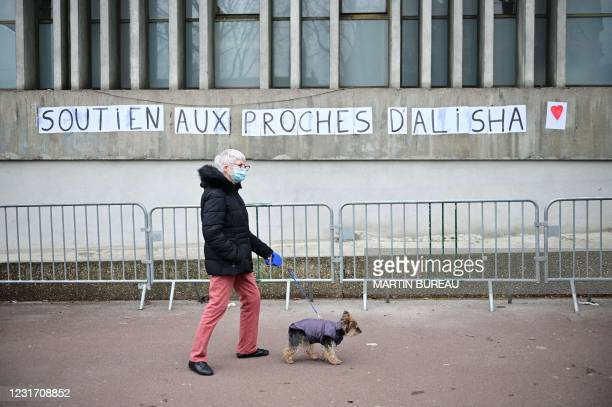 """Woman walks her dog past placards reading """"support to Alisha's relatives"""" on the sidelines of a white march in the memory of a 14-year-old girl,..."""