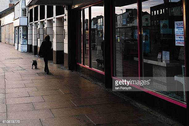 A woman walks her dog past shop fronts in Redcar high street on September 27 2016 in Redcar United Kingdom One year on since the SSI steel making...