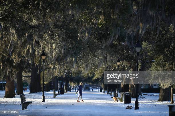 A woman walks her dog through a snow covered Forsyth Park as snow that fell yesterday and cold weather blanket the area on January 4 2018 in Savannah...