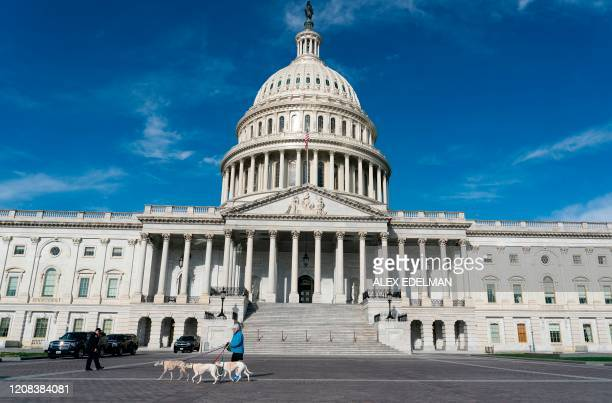 Woman walks her dogs near the US Capitol Building on March 27 in Washington, DC. - The US House of Representatives is expected to vote on a COVID-19...
