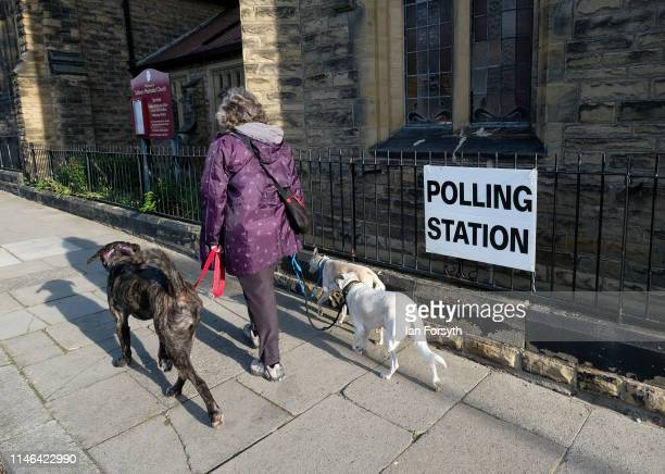 A woman walks her dogs past a polling station as they open during local elections on May 02 2019 in Saltburn By The Sea United Kingdom The elections...