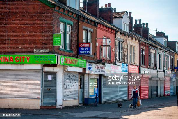 A woman walks her dogs past closed shops in Leeds city centre West Yorkshire on April 14 as life in Britain continues during the nationwide lockdown...