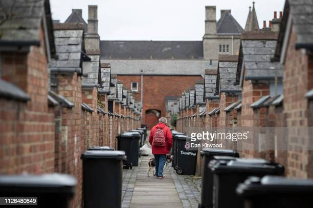 A woman walks her dogs through the back alley of an area of Housing known as the Railway Village on February 20 2019 in Swindon England The area once...