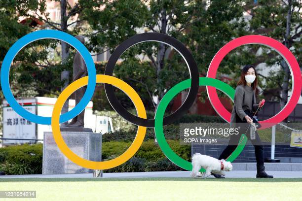 Woman walks her pet dog past the Olympic symbols of the five interlaced rings seen near the National Stadium in Tokyo. The government has decided to...