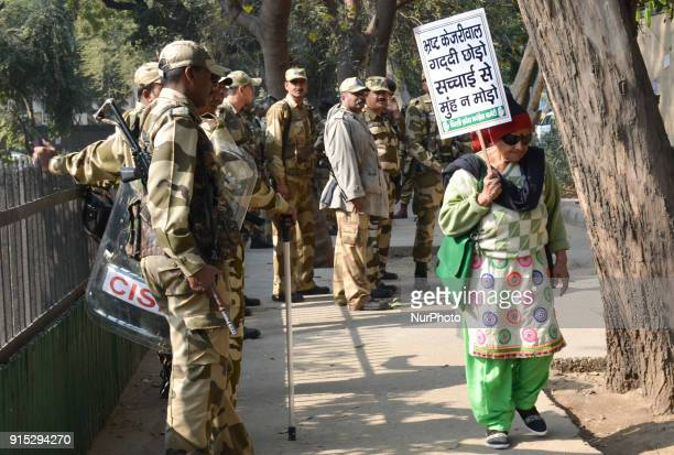 Woman walks holding a placard calling Aam Aadmi Party Delhi Chief Minister Arvind Kejriwal corrupts on corruption charges after a demonstration held...