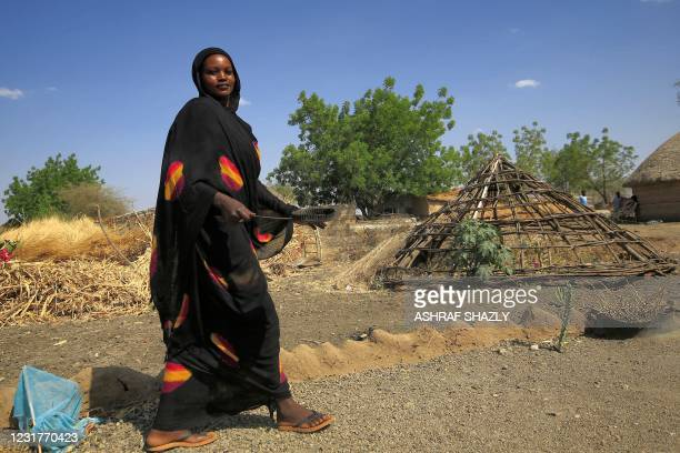 Woman walks holding a tray in the village of Dukouli within the Quraysha locality, located in the Fashaqa al-Sughra agricultural region of Sudan's...