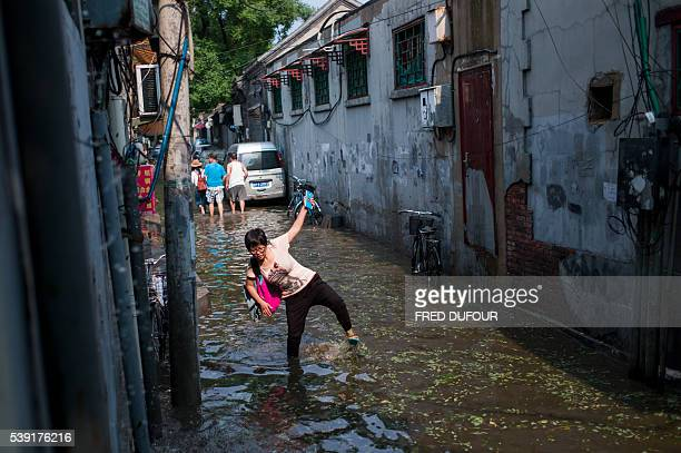 TOPSHOT A woman walks in a flooded street in a hutong after a heavy rain in Beijing on June 10 2016 / AFP / FRED DUFOUR