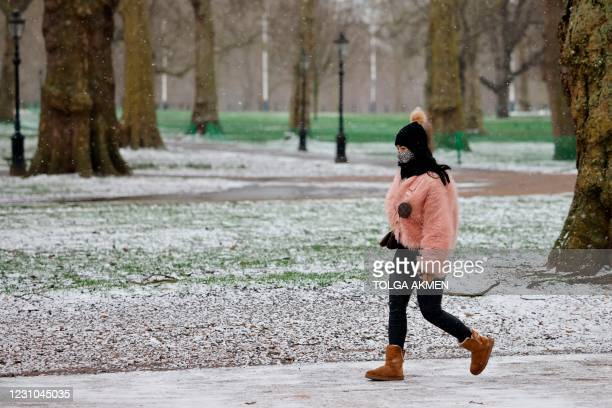 Woman walks in a park in the snow in central London on February 8, 2021. - Cold weather swept across northern Europe bring snow and ice.