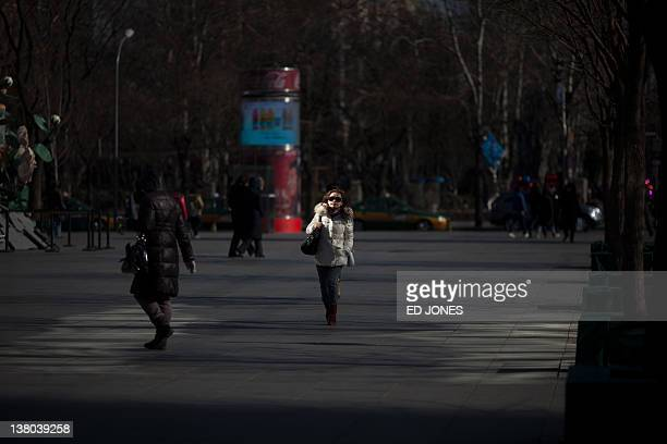 Woman walks in a popular shopping district of Beijing on February 1, 2012. On January 30 the IMF announced it had reduced its forecast for Chinese...
