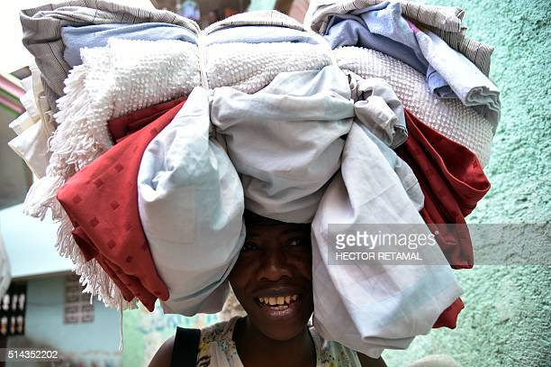 A woman walks in a small street selling her products in Jalousie neighbourhood in the commune of Petion Ville PortauPrince on March 8 2016...