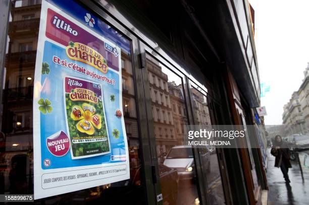 A woman walks in a street as a poster promoting a new scratchcard game called 'Jour de Chance' is on display on a window on January 3 2013 in Paris...