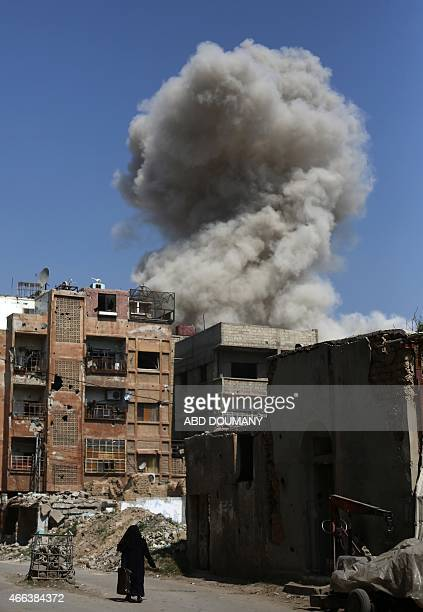 A woman walks in a street as smoke rises from buildings in the rebelheld area of Douma east of the Syrian capital Damascus following reported air...
