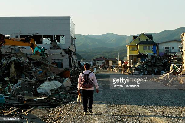 A woman walks in a stricken area that was devastated by the earthquake and tsunami that hit northeastern Japan on March 11 2011