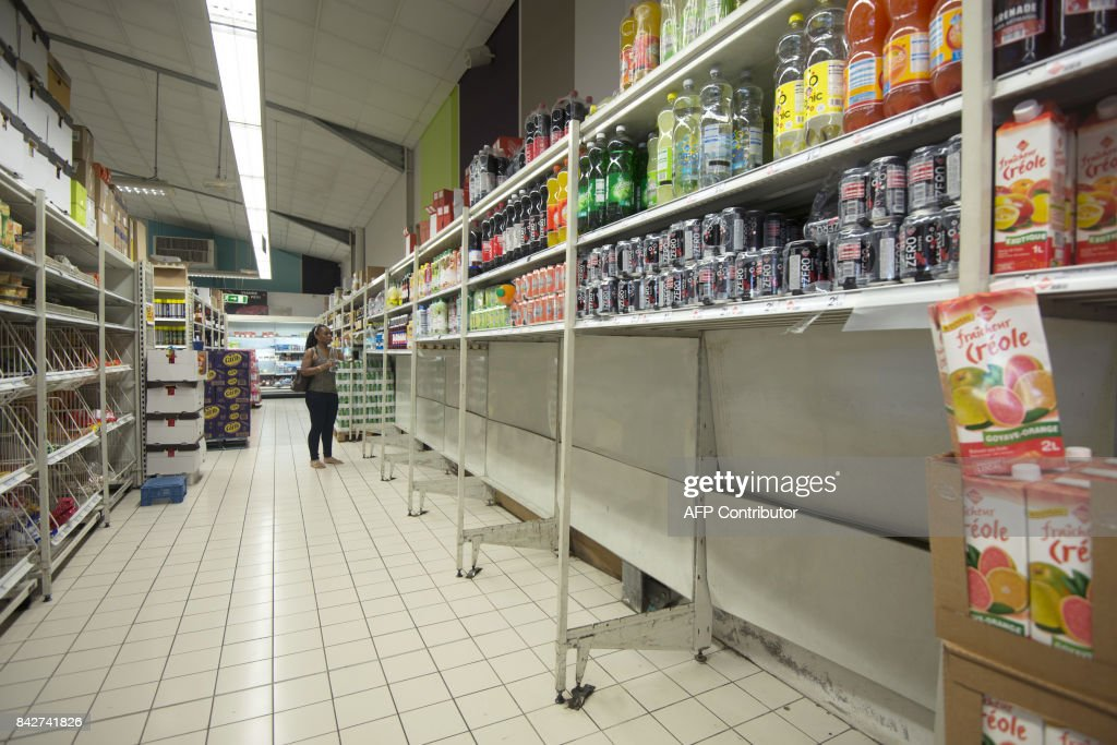 A woman walks in a supermarket where all packs of bottled water have been sold, in Pointe-a-Pitre, on the French overseas island of Guadeloupe on September 4, 2017, as part of preparations for arrival of Hurricane Irma. / AFP PHOTO / Helene Valenzuela