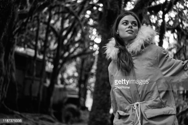 a woman walks in an old overgrown forest. black and white photo - dead raven stock photos and pictures