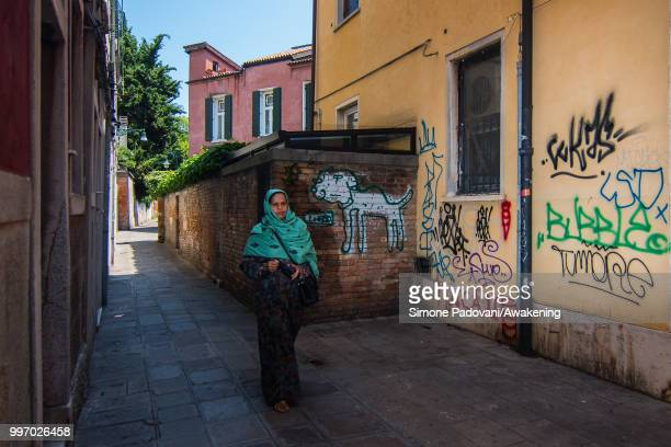 A woman walks in Calle Contarina where there are graffiti and tags on the walls on the way that connect University Ca' Foscari of Venice to railway...