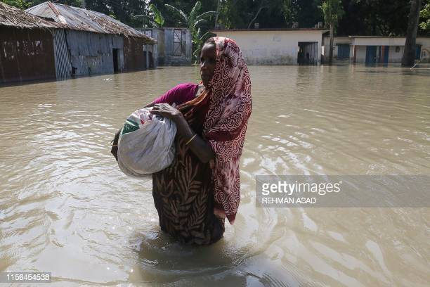 A woman walks in floodwaters as she holds a sac following heavy monsoon rains at a flood affected area of Gaibandha District in Northern Bangladesh...