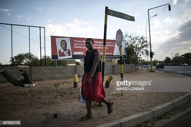 A woman walks in front of a billboard for the Botswana Democratic Party in the Marapula ward of Gaborone on October 21 2014 Two major parties...