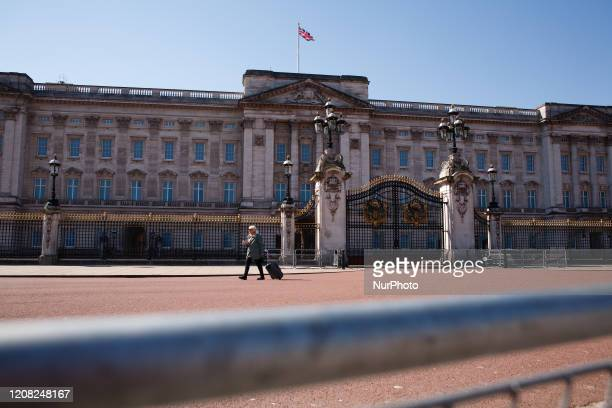 A woman walks in front of a deserted Buckingham Palace in London England on March 25 2020 Around a largely shutdown country the covid19 coronavirus...